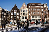 Amsterdam in winter. A woman pushes her bike over a bridge after a snowfall in Amsterdam, the Netherlands, 10 February 2013