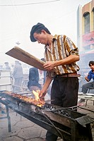 Uighur man cooking lamb skewers, Kashgar, Xinjiang province, China