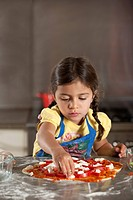 Young girl preparing a pizza