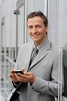 Europe, Germany, Bavaria, Businessman using mobile, smiling, portrait