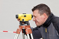 Mature man looking through theodolite