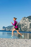 Italy, Mid adult woman jogging by Lake Garda