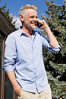 Germany, Berlin, Mature man talking on mobile phone, smiling