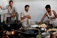 Workers in a sweet shop kitchen, India.