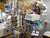 Room in an intensive care unit filled with multiple infusion pumps and monitors, as well as a ventilator and other equipment.