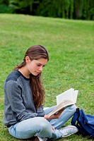 Young woman crossing her legs while reading a book