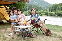 family sitting on camping chairs posing at camera