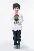 a young boy holding a red flower