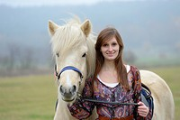 Smiling young woman with horse