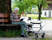 Austria, Senior woman sitting on bench and reading book