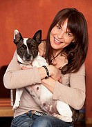 Portrait of mature woman holding pet dog, smiling