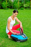 Young woman in garden operating robotic lawn mower