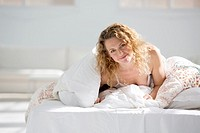 Attractive young woman wrapped in her quilt in bed