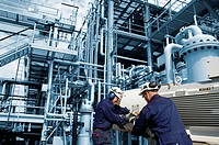 Two workers at a main pipeline pump inside large oil installation.