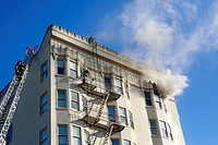 A fireman climbs to the top of a building to put out a fire.