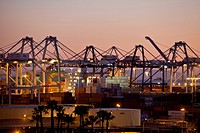 Cranes on horizon in Port of Long Beach at twilight.