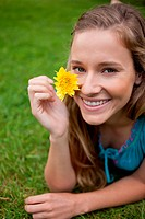 Smiling young woman showing a yellow flower while lying on the grass