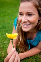 Young smiling girl looking away while lying on the grass and holding a flower