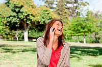 Woman laughing joyfully on a phone while standing in a sunny grassland area