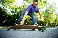 Young teenager rolling around on his longboard during the summer