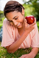 Woman looking downwards while presenting an apple