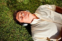 Man with his eyes closed while using headphones to listen to music as he lies do