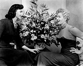 US actresses Shelley Winters and Colleen Miller, protagonists of the movie Playgirl by Joseph Pevney, before a big bunch of flowers. USA, 1954. Playgi...