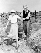 Barbara Stanwyck is helped to cross a path in the desert by Barry Sullivan while inspecting a site for the film Jeopardy. USA, 1953. Jeopardy, 1953 Di...