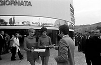 Two hostesses at the 48th Trade Fair distribuscono material front of the pavilion of Magneti Marelli. Milan, April 1970