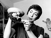 Italian artist and puppets designer Maria Perego making a puppet with her hand. 1950s.