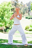 Smiling woman doing yoga exercises in the park