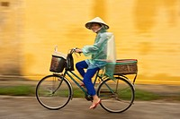 Vietnamese woman cycling in the rain, Hoi An, Vietnam