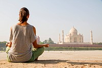 woman meditating close to Taj Mahal, India