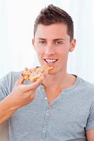 A smiling man holding pizza as he is about to eat