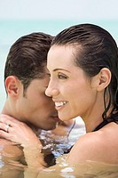 Hispanic couple hugging in water
