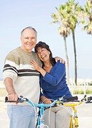 Couple walking bicycles on beach