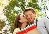 Woman kissing boyfriend in park