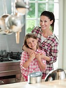 Woman hugging daughter in kitchen