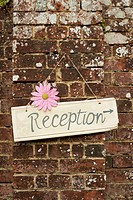 ´Reception´ sign on brick wall