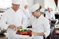 Chefs examining vegetables in restaurant kitchen