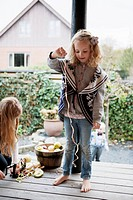 Girl playing with fruit peel on patio
