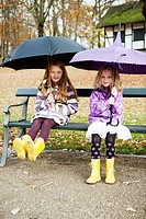 Girls in rain boots and umbrellas in park
