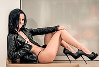 Sexy naked girl wearing high heels shoes and leather jacket posing indoors