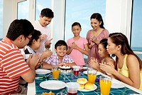 Group of people at party table celebrating birthday