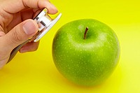 Close-up of hand holding stethoscope to a green apple