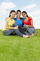 Three young women sitting on the grass, smiling at the camera