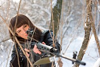 Portrait of girl with a sniper rifle in winter forest