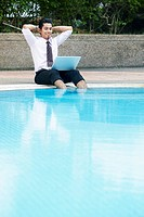 Young businessman using laptop by the swimming pool