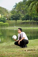 Young businessman squatting and holding a football