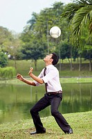 Young businessman heading soccer ball with his head